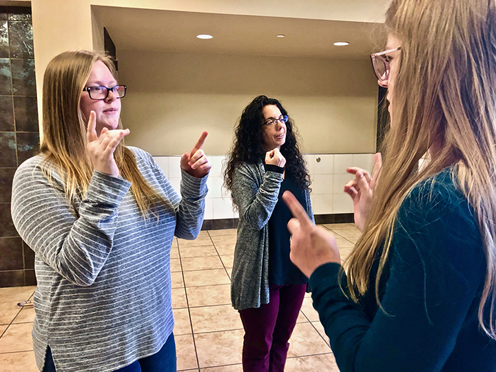 Reagan Brooks, left, and Erica Haase, right, and Amber Marchut, deaf studies and deaf education assistant professor, middle, converse in ASL, in the Communications Building, Nov. 19. UP photo by Vy Nguyen