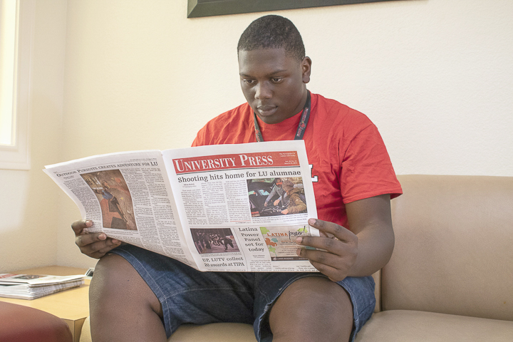 Daniel Johnson, Beaumont freshman, reads a copy of the University Press in the lobby of Gentry Hall, Sunday. UP photo by Caden Moran