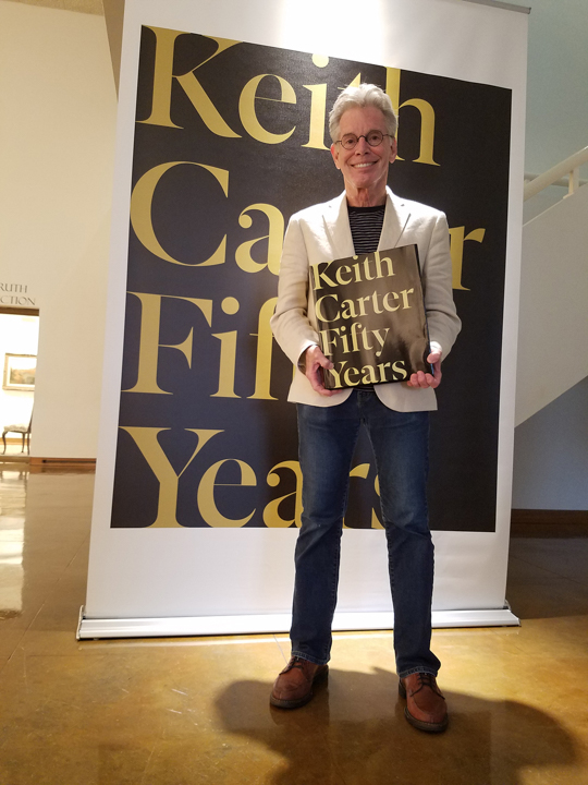 Keith Carter stands with a copy of his retrospective book in the Dishman Art Museum, which is hosting an exhibition of the same name. UP photo by Sierra Kondos