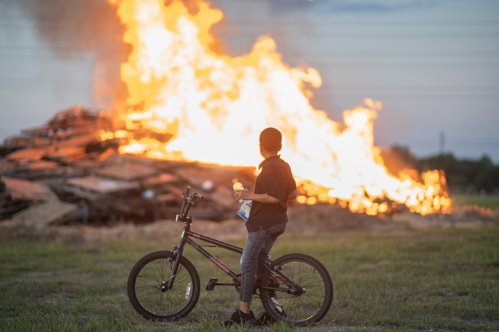 A student on a bike watches the bonfire burn at Lamar University's Homecoming Pep Rally and Bonfire, Sept. 27. UP photo by Noah Dawlearn