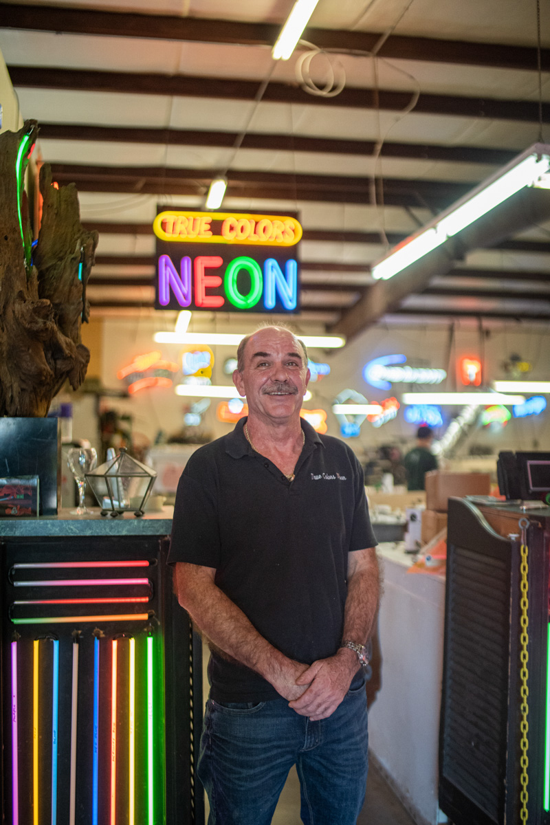Dobelmann stands in front of the entrance to his shop, next to a test kit of the diffrent types of neon his shop provides near Richmond Ave. in Houston, Oct. 18.