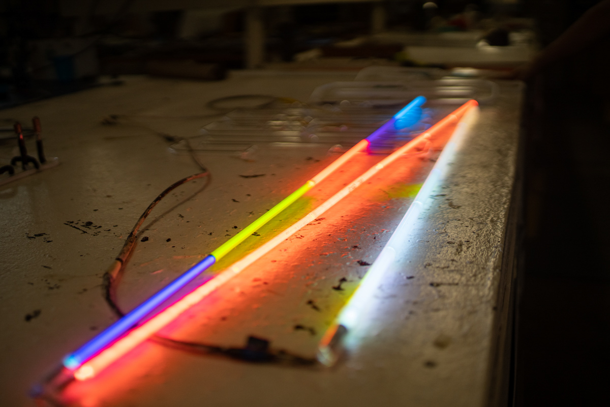 Dobelmann lights up three pieces of glass tubing, one with different colored glass, another with a clear piece of glass with a color powder filled with neon, and a final tube with glass and powdered color to filled with argon to show how the different gasses affect the colors.