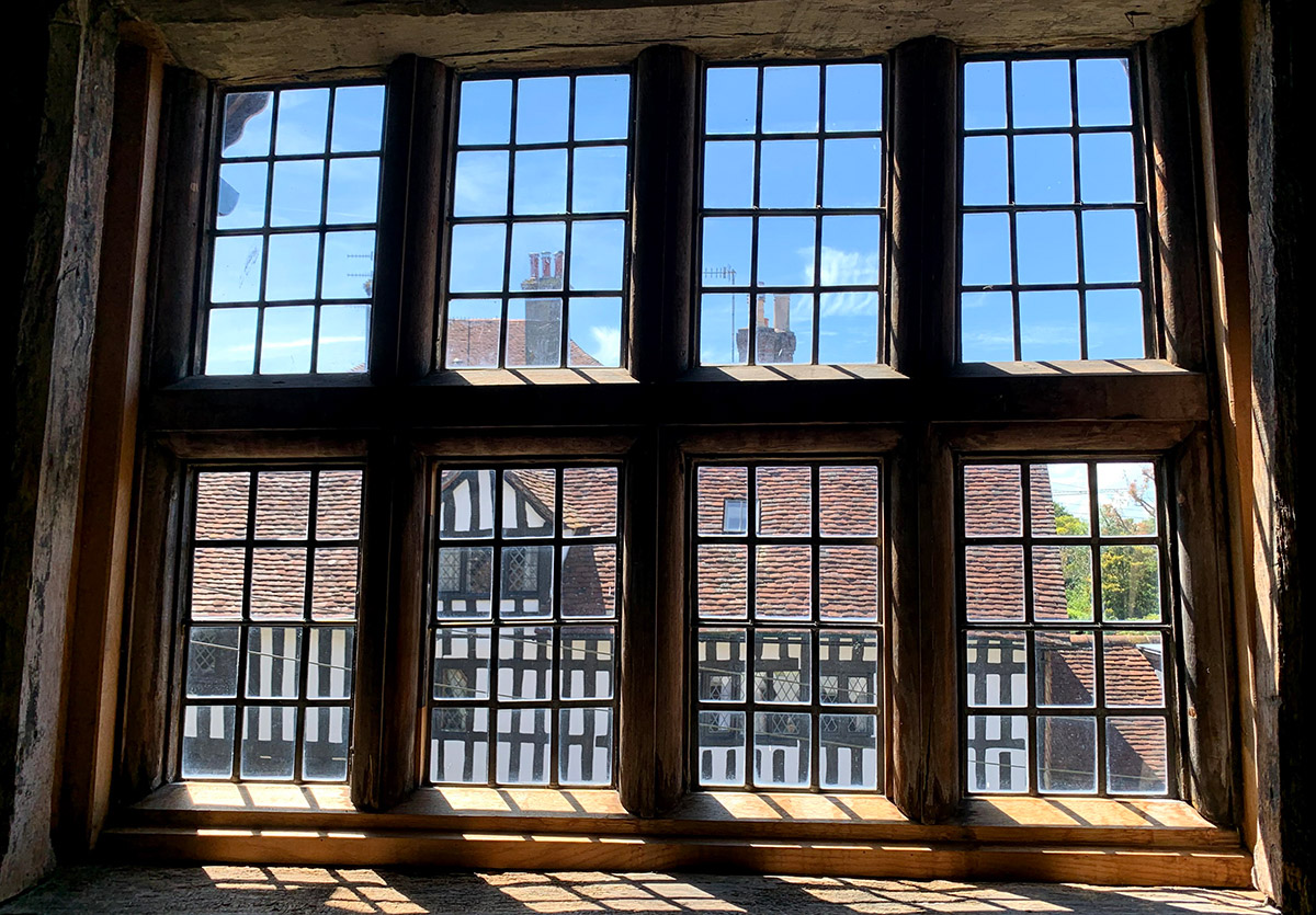 The exterior of the Anne of Cleves House, left, can be seen through the windows of an adjacent building exhibiting more artifacts of the time.