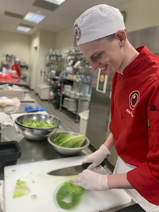 Philip Parsons, Anahuac junior, right, prepares a meal for the Cardinals on the Run meal program, Monday. UP photo by Christina Segura