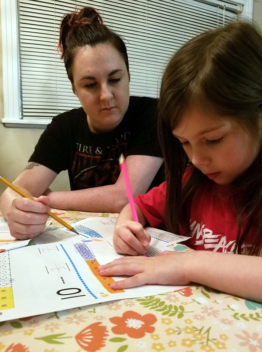 LU student Rachel Hellums works works with her daughter on school work at home. Courtesy photo