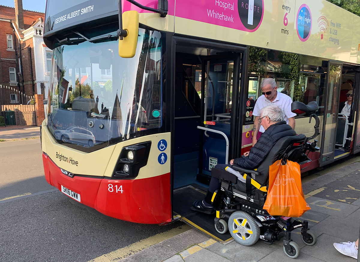 A bus driver assists a passenger in a wheelchair on theBrighton bus service.